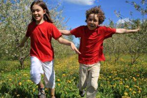 Kids running, jumping on green meadow (photo by Jacek Chabraszewski)